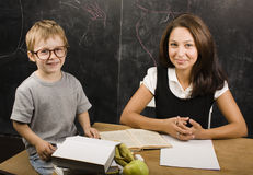 Little cute boy with teacher in classroom Stock Photos