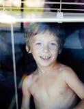 Little cute boy throught window royalty free stock photos