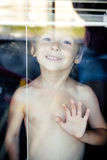 Little cute boy throught window making funny faces, home alone lifestyle concept Royalty Free Stock Image