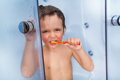 Little cute boy use toothbrush in shower cabin. Little boy brushing tooth with brush standing in the hotel shower cabin behind glass door and looking at camera stock photography