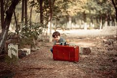 Little cute boy in vintage clothes peeking from behind a retro suitcase. On the suitcase is a vintage camera.  stock images