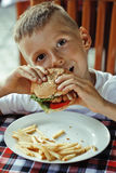 Little cute boy 6 years old with hamburger and Stock Photography