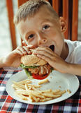 Little cute boy 6 years old with hamburger and Royalty Free Stock Image