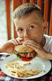 Little cute boy 6 years old with hamburger and Stock Photo