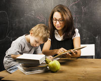 Little cute boy with young teacher in classroom studying at blac Royalty Free Stock Images