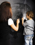 Little cute boy with young teacher in classroom studying at blac Stock Image