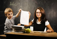 Little cute boy with young teacher in classroom studying at blac Royalty Free Stock Photo