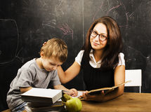 Little cute boy with young teacher in classroom studying at blac Stock Photo