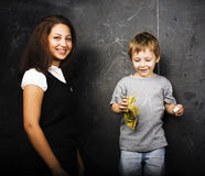 Little cute boy with young teacher in classroom studying at blac Stock Photography
