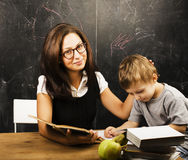 Little cute boy with young teacher in classroom studying at blac Royalty Free Stock Photos