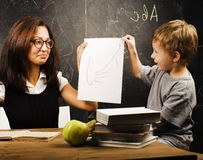 Little cute boy with young teacher in classroom studying at blackboard smiling, lifestyle people concept Stock Image