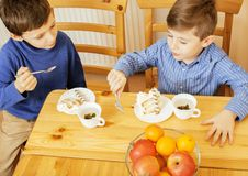 Little cute boys eating dessert on wooden kitchen. home interior Stock Photography