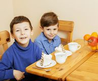 Little cute boys eating dessert on wooden kitchen. home interior Royalty Free Stock Photography