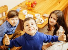Little cute boys eating dessert on wooden kitchen. home interior. smiling adorable friendship together forever friends stock photography