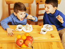Little cute boys eating dessert on wooden kitchen. home interior Royalty Free Stock Photo