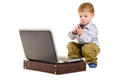 Little cute businessman. Cute small boy dials on a mobile phone while sitting next to laptop Stock Photography
