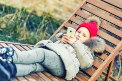 Little cute caucasian blonde toddler girl in red  knitted hat and warm jacket lying over lounge and holding smartphon in hand.  Ou. Tdoor liesure. Child social Royalty Free Stock Photos