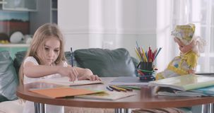 Little cute Caucasian girl doing math at home. Pretty child writing figures in exercise book and thinking. Intelligence stock video footage