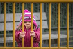 Cute girl behind bars royalty free stock photo
