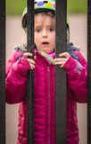 Scared girl behind bars royalty free stock images