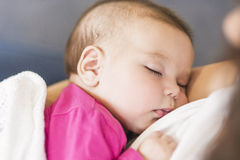 Little Cute Caucasian Infant Sleeping on Mothers Hands Indoors. Royalty Free Stock Photography