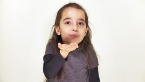 Little cute cheerful girl sends an air kiss and looks at the camera, white background 50 fps stock footage