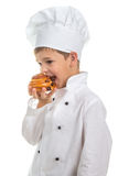 Little cute chef cooker eating delicious fresh raisin bun, isolated on white. Background Royalty Free Stock Image