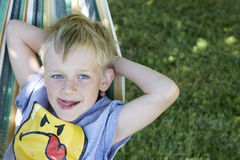 Little cute child blond  boy swinging and relaxing on a hammock Stock Photo