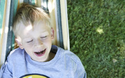 Little cute child blond  boy swinging and relaxing on a hammock Stock Images