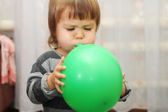 Little cute child blow a ball Royalty Free Stock Photography