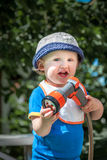 Little cute child in blue hat holding a garden hose outdoors sunny summer day. royalty free stock images