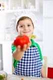 Little cute child boy with cook hat holding tomato Stock Photo