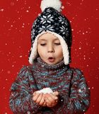 Little cute child boy is holding snow in hands wearing warm clothes and hat isolated on red background stock images