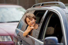 Little cute child, boy, looking out the window of a car. Smiling Stock Images