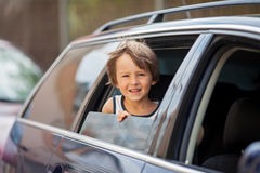 Little cute child, boy, looking out the window of a car. Smiling Stock Photo