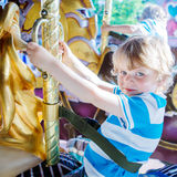 Little cute child during carousel ride, enjoying and having fun Royalty Free Stock Photos