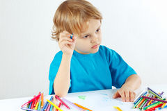 Little cute child draws with color pencils Royalty Free Stock Images