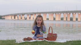 Little cute child girl eating fresh fruit during picnic near river on background of bridge. Little cute child girl eating fresh fruit during picnic outdoors near stock video footage