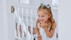 Little cute child girl peeks through the doorway in room with funny emotions.  royalty free stock image