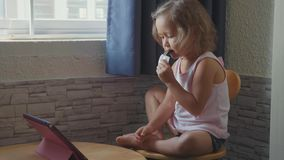 Little cute child girl watching something in the tablet and eats fruit bar. Little cute child girl watching something in the tablet and eats fruit snack bar next stock footage
