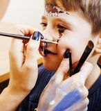 Little cute child making facepaint on birthday party, zombie Apo Stock Image