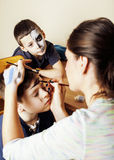 Little cute child making facepaint on birthday party, zombie Apocalypse facepainting, halloween preparing concept. At home Stock Photos