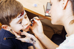 Little cute child making facepaint on birthday party, zombie Apocalypse facepainting, halloween preparing concept. At home Stock Photography