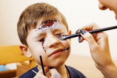 Little cute child making facepaint on birthday party, zombie Apocalypse facepainting, halloween preparing concept. At home Stock Images