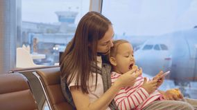 Mother feeds her little daughter with tangerine at airport. Little cute child sits on mothers`s hands and play games on smart phone while mother feeds her with Royalty Free Stock Photos