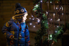 Little cute child standing outdoors at Christmas time with illum Stock Photography
