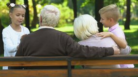 Little cute children happily talking with grandparents sitting on bench in park stock footage