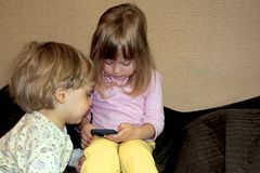 Little cute curious blonde twins watch cartoons on smartphone. Home photo royalty free stock images