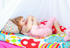 Little cute curly girl in pink pajamas lying in a baby bed Royalty Free Stock Image