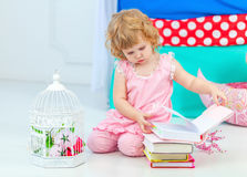 Little cute curly girl in pink pajamas watching the book sitting on the floor in children's bedroom. stock photos